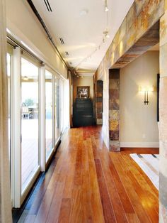Hallway Lighting: Sunlight streams from the interior courtyard into the long hallway while elegant track lighting casts a subtle glow. From HGTVRemodels.com