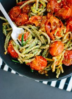 Delicious summertime pasta dish with pesto, squash noodles and spaghetti with burst cherry tomatoes