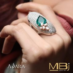 Cocktail diamond ring with round & pear shaped diamonds along with emerald.