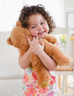 Toddler hugging teddy bear, smiling.