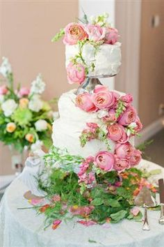 Cake love: a romantic wedding cake covered with pink roses and foxgloves