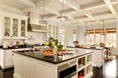 Expansive kitchen with two island and matching chic pendant lamps with stylish finishes.
