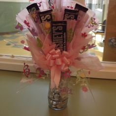 On a skewer tapes heresy's bar with tissue backing it. Fill a vase with chocolate kisses, arrange skewers as if they were flowers!