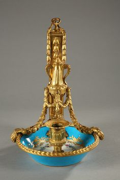 An eighteenth century portable candlestick in Sèvres porcelain with its ormolu mount and a two-handled candle snuffer cone. The porcelain is decorated with garlands of flowers, foliage, polychrome leaves...