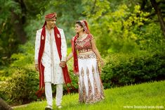 This Indian bride and groom have a traditional Indian wedding ceremony with classic outfits including a red and white sari for the bride and a matching sherwani for the groom. For the reception they choose a purple theme with white floral arrangements.