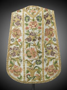Set of liturgical vestments (cope, chasuble, burse, maniple, chalice veil, cope hood) about 1760 Chasuble: Off-white silk and silver chasuble embroidered with pink, purple, green, and gold floral and cornucopia motifs. Trimmed in thick gold embroidery.
