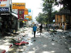 People walking on commercial street in Phuket, Thailand, amid debris strewn about by tsunami (© AP Images)