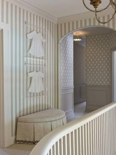 Beautifully framed baby clothes-and love the hallway stenciling too.