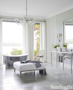 """""""I love a glamorous bathroom,"""" designer Marshall Watson says. He turned the master bath in a Florida house into a open-air oasis with floor-to-ceiling windows, cast-iron tub, custom vanity, and crystal chandelier."""