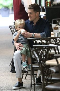 Daddy's boy: Michael carries his son and feeds him some milk during their day out on Tuesday