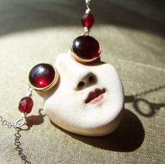Felicia Nilson, Ruby Eyes.  Small face pendant with antique shirt studs as goggles or sunglasses.