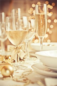 Champagne-filled glasses with gold baubles, bows and garlands scattered across the table to provide the reception decor.
