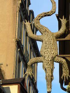 L'enseigne du restaurant « Au crocodile » 10 rue de l'Outre. Elle date de 1979 et est faite en laiton et bronze doré à la feuille.