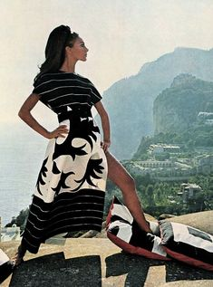 Marisa Berenson photographed in Capri wearing a black-white print silk cape-coat by Forquet, 1968