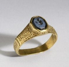 """12th century Byzantine ring. Gold and cameo. The hoop of this large signet ring is decorated with scrollwork. The sides of the octagonal bezel, which is framed by two lions at the shoulders, are inscribed in Greek with a quotation from Psalm 26: """"Lord, my Light and my Savior, whom shall I fear?"""" In contrast to this Christian motto, the intaglio depicts the pagan god Pan, who is represented as an older bearded man with goat's legs and his characteristic pipes. Accession no 57.1580"""