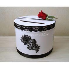 Raffinée, cette urne sera idéale pour un mariage au thème baroque et cinéma. Réalisée sous la forme d'une boite à chapeau, cette urne est ornée de dentelle noire et d'une rose rouge.