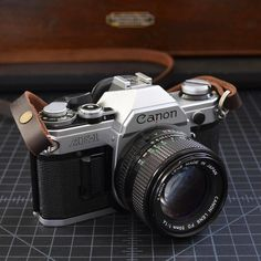 Canon AE-1 A 35mm film SLR camera produced in Japan by Canon between 1976-1984. This is a historically significant SLR because it was the first to be equipped with a microporcessor and because it sold over one-million units - an unprecedented success in the SLR market. This one features a Canon FD 50mm f/1.8 lens and Talbott & Sons fixed length leather camera strap.