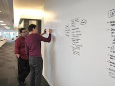 White-board walls are located throughout the space, allowing employees such as Gary Cartagena (left) and Donovan Walker to discuss ideas. [Gensler]