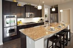 Dark cabinets in varied heights contrast with stainless steel appliances. Pendant lamps add light over a gleaming island. The Notting Hill Community by Pulte Homes. Eden Prairies, MN.