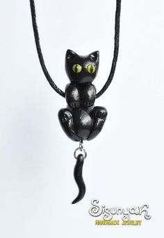 Funny Black hanging cat necklace, hand made of polymer clay. Length is adjustable. Measurements: Head is about 1 cm in diameter. Body - about 2 cm. Tail with hooks - about 2 cm. From the ears to the end of the tail - about 4.7 cm.  Check out the matching Black Cat Earrings: https://www.etsy.com/listing/114600070/black-cat-clinging-earrings-kuroneko?  The shipping method is registered priority mail.  All items arrive nicely packaged in a hand made origami box.