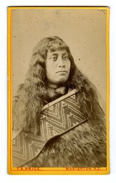 Photograph (black and white); portrait of a Maori girl; wearing neck tie and woven cloak with Taniko borders; New Zealand.