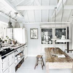 White kitchen with distressed farm table, hanging fixtures and open cabinetry.