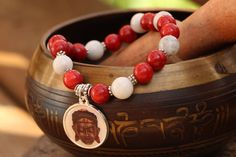 What you see is what you get - this is the only one of this bracelet I will make! Get it before its gone! - Gautama Buddha charm. - Genuine red coral beads. - Genuine Malaysian jade white beads. - 7 Inches un-stretched (approximately). This bracelet best fits people with a medium or large frame. - Ships from Canada.  This bracelet has an inspirational Buddha charm with a calming face, genuine red coral beads that give you vitality, and white Malaysian jade beads that give you clarity. This…