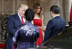 Both men wore dark suits, while the American first lady sported a red tea-length dress, pa...