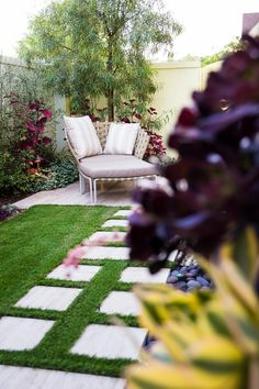 Stone pavers in grass lead to a quite corner of the backyard where a woven outdoor chair sits. Purple leaf plants and lilac seat cushions compliment each other, creating a zen atmosphere.