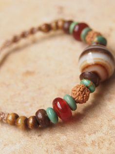 アゲートのビーズブレスレット縞模様の美しいアゲート(瑪瑙石)のビーズをメインにしたビーズブレスレットです。アゲートは大地を象徴する天然石で安定した穏やかな気持ちにさせてくれると言われてます。ターコイズやカーネリアンの天然石のほか、菩提樹の実やボーンビーズなどの自然素材を使ったどこか土の香りのする落ち着いた印象のブレスレットに仕上がりました。
