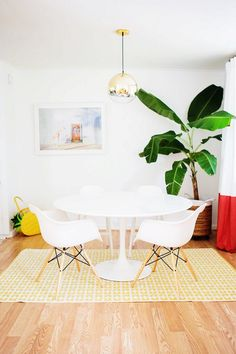 Chic dinning space with a bright yellow area rug, a gold pendant light, and mod white chairs