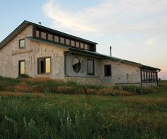 """Yet -to-be-completed straw bale house on a ranch in the Flint Hills of Kansas.  South-facing clerestory windows bring light and winter heat deep into the north rooms. The final """"color coat"""" of cement-lime stucco is still to be applied. The rough coat shows the result of many hands helping at the owner's plastering parties. The bales were made of native grasses."""