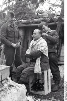 Who said that battle interrupts civilian life routines? Luftwaffe airman as barber gives a quick cut to a comrade sitting on a half empty case of wine bottles. A well prepared field wooden cabin can be seen in the background. 1920s Photos, Photos Du, Old Photos, Luftwaffe, Guys Grooming, Second World, Military History, Barber Shop, World War Ii