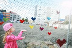 craft bombing yarn hearts onto a chain link fence.