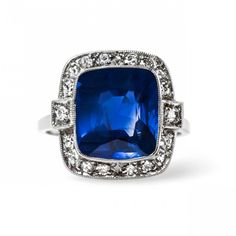 Gorgeous Unheated Sapphire Engagement Ring Lausanne: An incredible vintage Late Art Deco (c.1935) 14k W gold ring. This show-stopping ring centres a bezel set 6.82ct Cush Cut sapphire. GIA certified. The sapphire is unheated from Madagascar, an extreme rarity. The sapphire exhibits silks within the stone, a clarity characteristic described as microscopic rutile needles, these are highly reflective & scatter light within the faceted stone A halo of 18 Single cut diam frame the stunning…