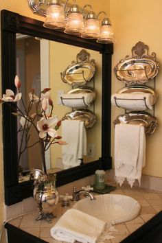 DIY Add Molding & Wooden Square Medallions To Your Plain Bathroom Mirror For A Designer Look. For a little extra pizazz, put thrift store vintage silver trays in the back of the wall towel racks for extra flair.
