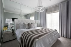 source: Adore Magazine website    Gorgeous bedroom with floor to ceiling mirrors framing white tufted headboard accented with gray faux fur throw blanket and gray quatrefoil pillows flanked by Bourgie Table Lamps on mirrored nightstands. Master bedroom features crystal beaded chandelier as well as gray curtains.