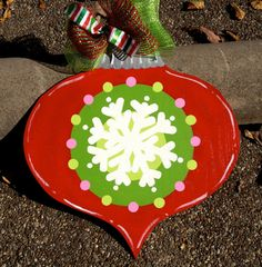 "Hand Painted Wooden Christmas Ornament Door Decoration by LuluAnns, $55.00 Brighten your door for the holidays with my hand painted, hand cut wooden Christmas ornament. Painted in shiny red, two shades of green and pink with a big white snowflake in the center, this decoration will liven up your doorway throughout the season! It measures 22""x21"" and has about a 4"" drop from the wire hanger trimmed in mesh ribbon. The back is unpainted unless otherwise requested.  Happy Holidays!!"