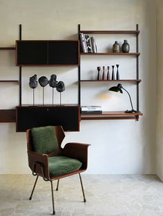 Kai Kristiansen teak shelving system FM Mobler 1960 - Italian armchair, 1950 c.a. - Kaiser Idell desk lamp, Christian Dell - Danish ceramics - Italian ceramics black sculptures - www.capperidicasa.com