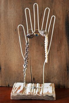 She purchased 1940's Wire Glove Dryers and mounted them to make jewelry stands. Could easily use a white wire hanger and make your own display!