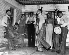 In this July 12, 1937 file photo, the eight men due to be arraigned before the Circuit Court in Decatur, Ala. play music at their jail in Birmingham, Ala. before their court appearance. From left are Olen Montgomery, Andy Wright, Eugene Williams, Charlie Weems, Patterson, Clarence Norris (dancing) Roy Wright, Ozie Powell and Willie Roberson, also known as the Scottsboro Boys.