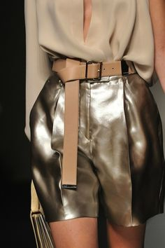 taupe billowy blouse, pewter liquid leather metallic shorts, tan leather belt cinched at waist