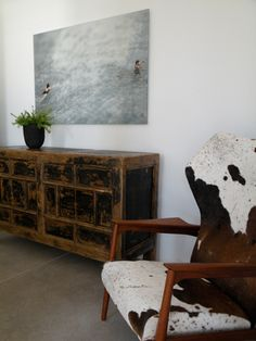 Hide chair, vintage console and contemporary art