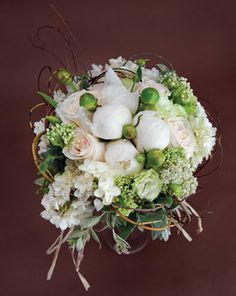 snow white    White peonies and buds, blush garden roses, cream lisianthus, white asclepias, thistle, lambs ear, and Star of Bethlehem all wrapped together with bent curly willow. By Diana Gould Ltd, Elmsford.
