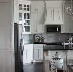 I love this kitchen, the white cabinets with some glass doors, marble tile backsplash, dark floors, pendants. I also love the white and grey chinoiserie vase in the foreground! New Kitchen, Kitchen Renovation, Kitchen Decor, Home, Kitchen Remodel, Kitchen Vent Hood, Home Kitchens, Kitchen Redo, Kitchen Inspirations