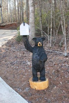 Bear holding mailbox -- not quite like the one Jay carved for the Silver Bear Shop, but quite realistic and cool!Chainsaw-carved Bear holding mailbox -- not quite like the one Jay carved for the Silver Bear Shop, but quite realistic and cool! Home Mailboxes, Unique Mailboxes, Black Bear Decor, Bear Shop, Tree Carving, Mailbox Ideas, Mail Boxes, Wood Art, Wood Projects