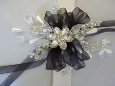 A beautiful wrist corsage which will add a touch of glamour to any special event whether it be a wedding or a prom. Its centrepiece is a sparkling silver flower brooch and it is surrounded by beads and jewels adding extra shimmer and shine. This wrist corsage is finished off with black ribbon but the ribbon can be changed to match the occasion or the outfit. This is made on a snap band to fit any wrist.