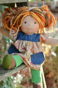 This is Franny.  She has sunkissed skin, long hair made with mohair, variegated dreadlocks and wool yarns in a multi-tonal ginger color with and brown eyes.  She is wearing the pictured outfit, underpants and wool felt shoes.