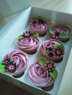 Cupcakes con cubierta en crema en forma de rosa color lila , motivo decoración en flores y hojas