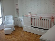 Quarto de bebê, quarto de menina. Com armário e berço brancos, poltrona branca, papel de parede, e piso de madeira. Arquiteta Danyela Corrêa